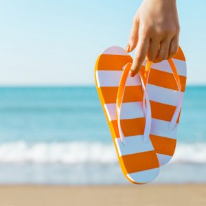 Woman's hand holding a pair of orange sandals against the coastline