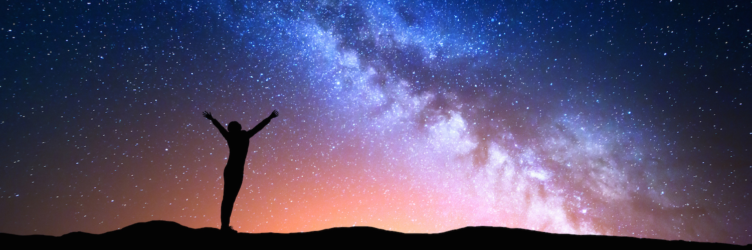 Illustration of colorful night sky with Milky Way pictured and a silhouette of a woman standing underneath it with arms raised