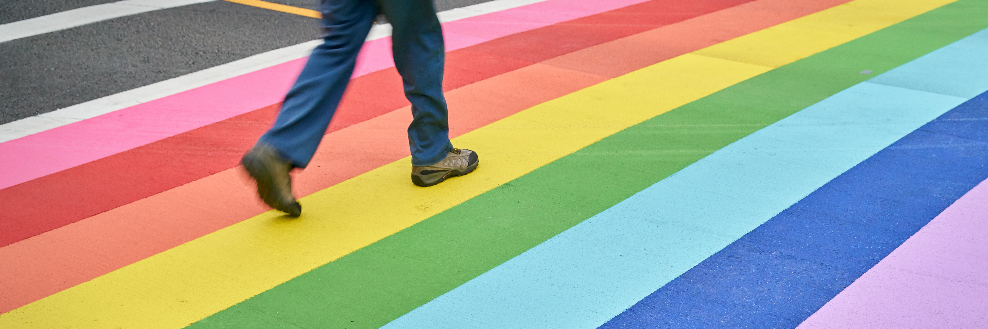 A pedestrian using the rainbow colored crosswalk in downtown Vancouver.
