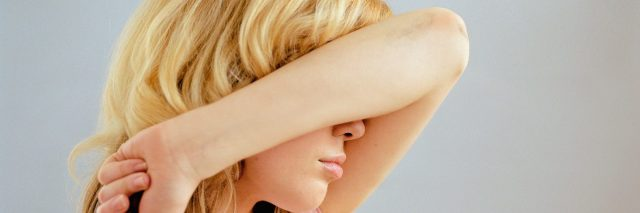blonde woman covering face with arm