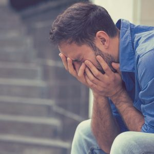 man sitting outside crying with head in hands
