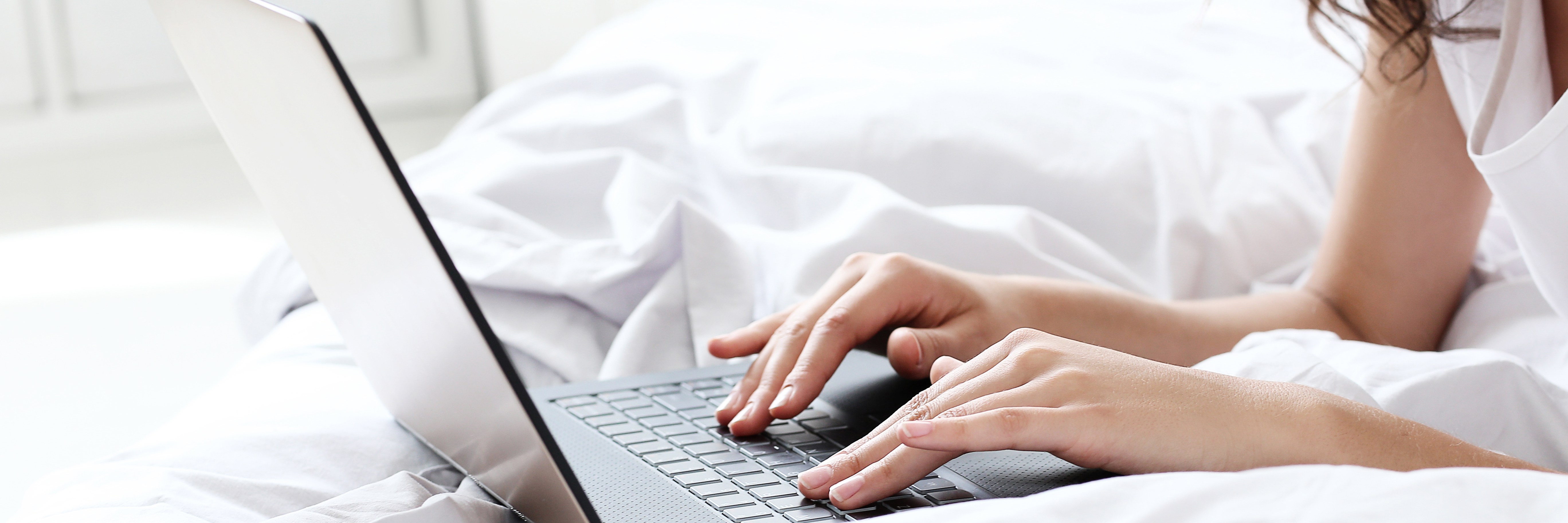 close up of woman working on laptop while lying on bed
