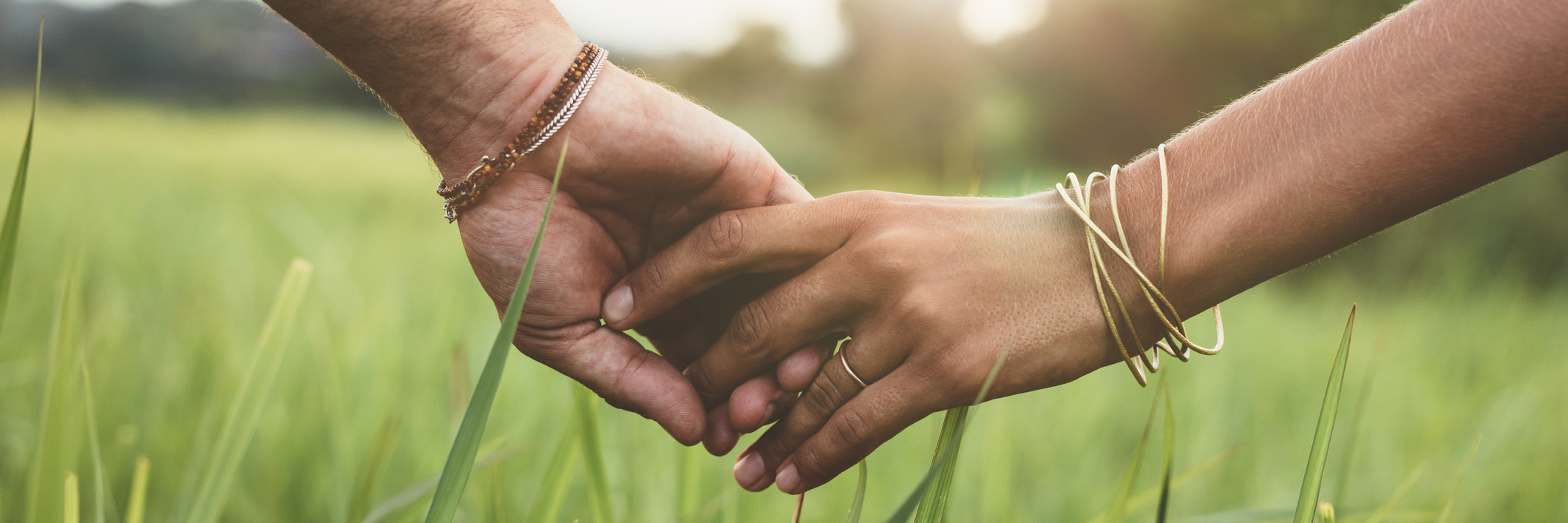 Man and wife holding hands, walking in a grassy field.