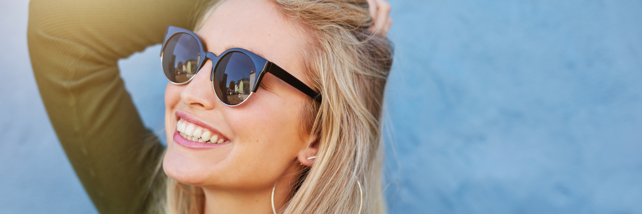 A woman wearing sunglasses, smiling.