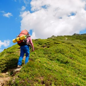 woman hiking up a hill at a steep incline