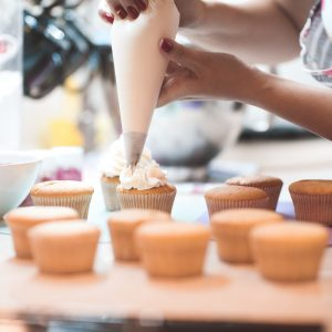 woman frosting a batch of cupcakes