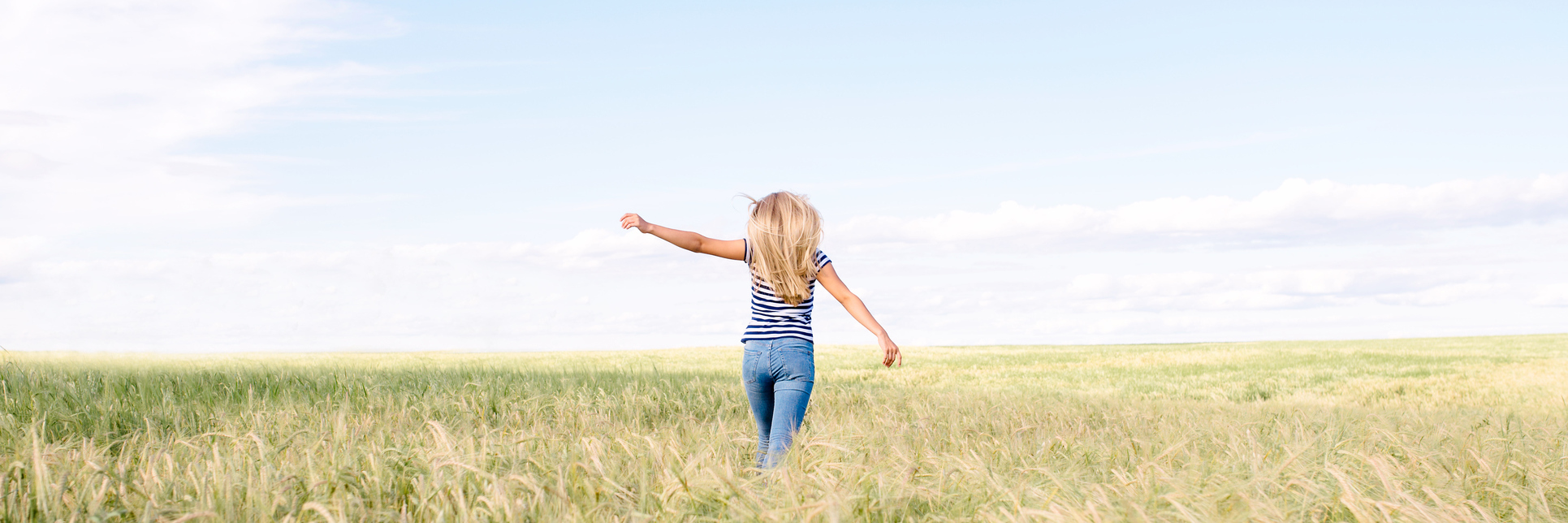 young blonde woman with arms outstretched in field