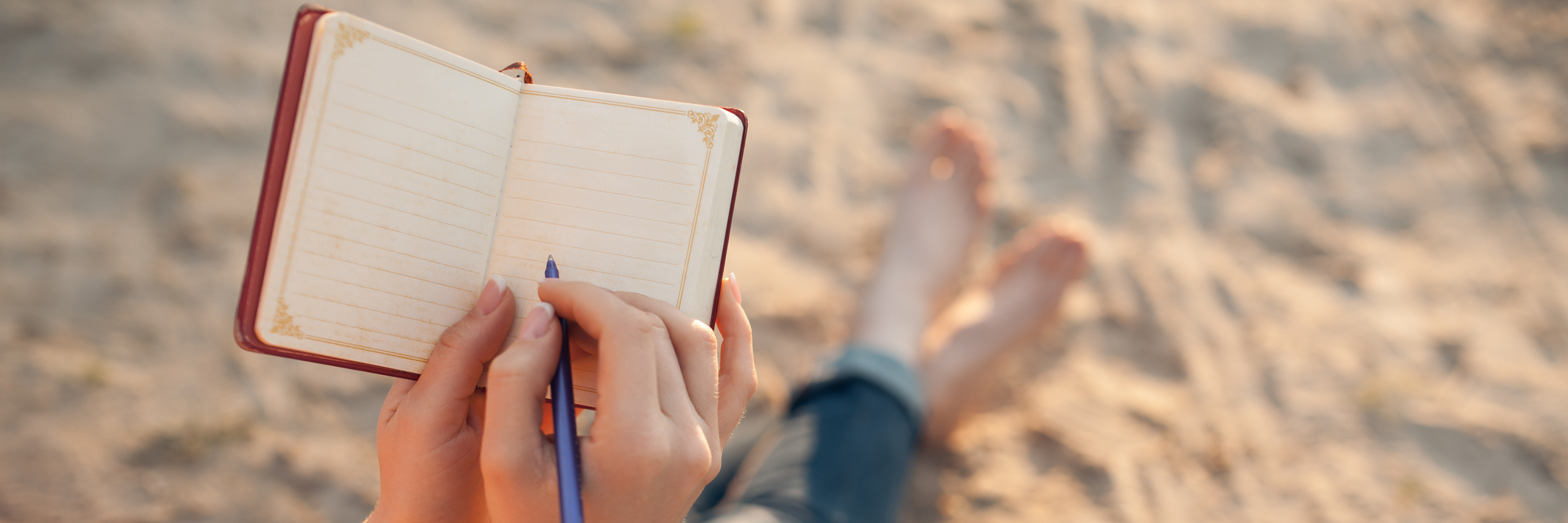 Young woman sitting on the beach writing.