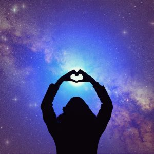 Silhouette of woman making heart shape with hands, with arms extended toward starry night sky