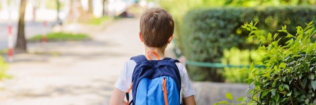young boy wearing a backpack and walking to school