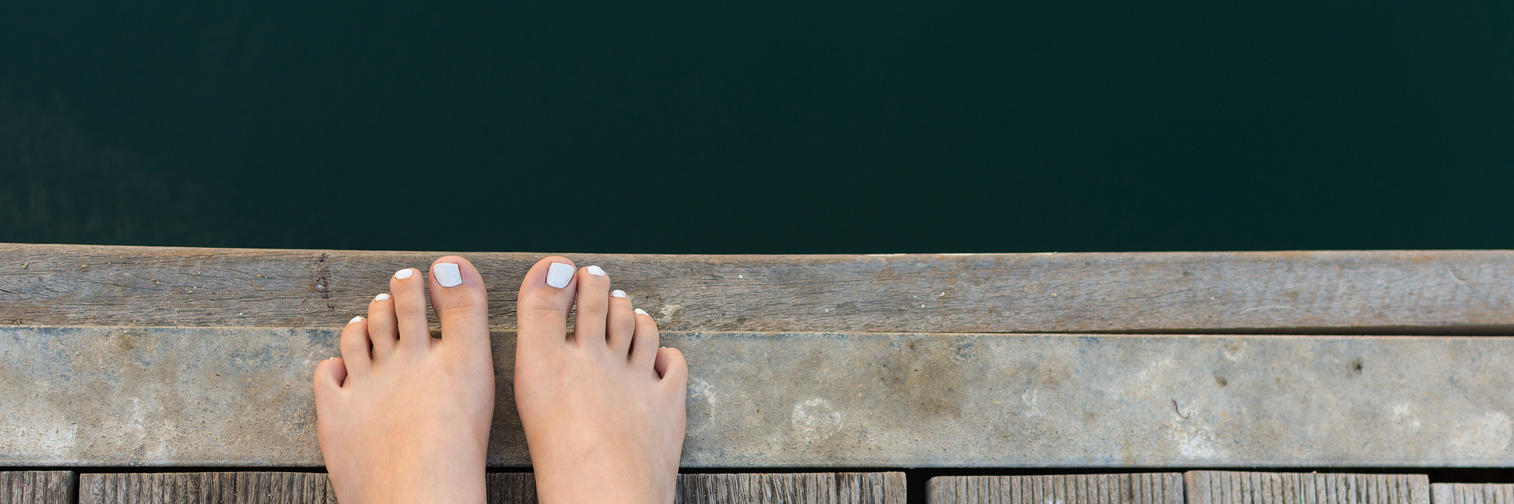 woman's feet on wooden pier overlooking water