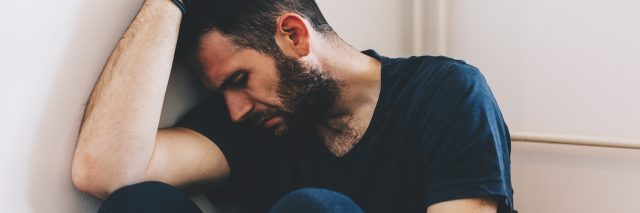 man with depression sitting in corner of room resting head on arm