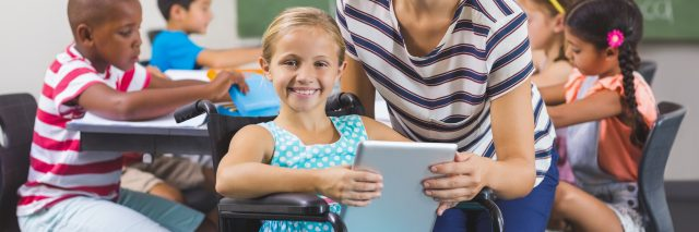 Girl and teacher using AAC tablet in classroom.