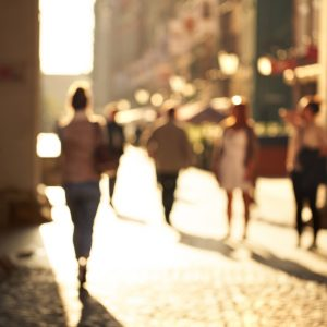 Blurred background of unrecognizable persons rushing through the arch on the touristic street.