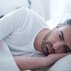 depressed man lying in bed wide awake