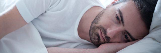 depressed man lying in bed wide awake