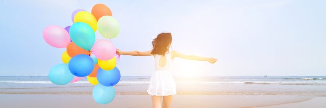 Woman at the beach, walking on the shore with vibrant balloons.