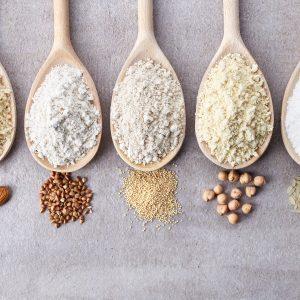 Wooden spoons of various gluten free flour (almond flour, amaranth seeds flour, buckwheat flour, rice flour, chick peas flour) from top view.