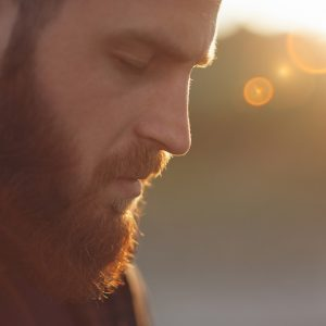 man with red beard standing outside in the sunlight