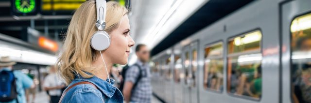 A woman with her earphones in waiting for a subway