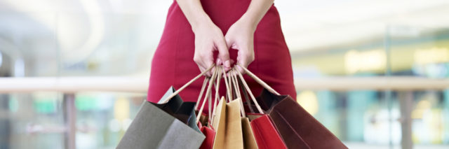 young woman female shopper standing with colorful paper bags in hands in shopping mall or department store, focus on hands