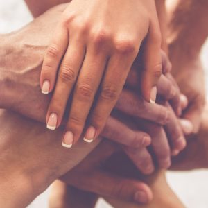 Hands stacked on top of each other in supportive gesture