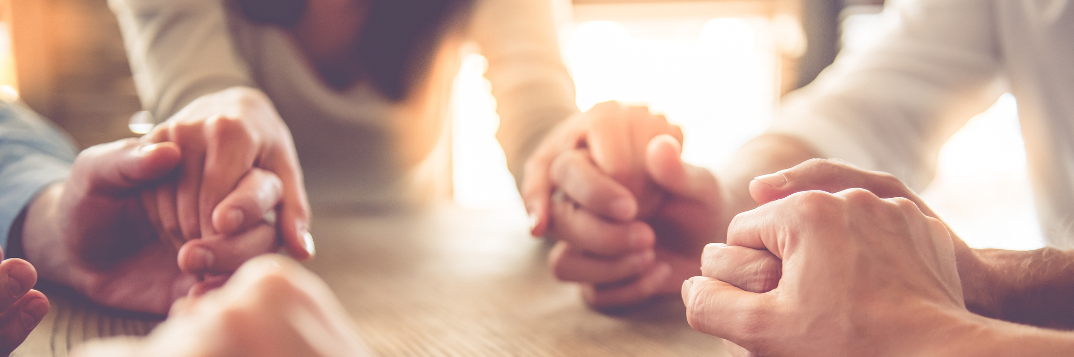 close up image of business team holding hands together on wooden table in warm light