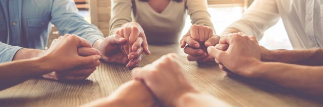 group of people holding hands around table in soft light