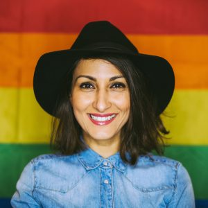 A woman wearing a cowboy hat smiling in front of a rainbow gay pride flag