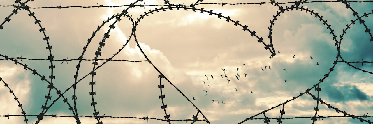 heart shape in a barbed wire fence against a sky