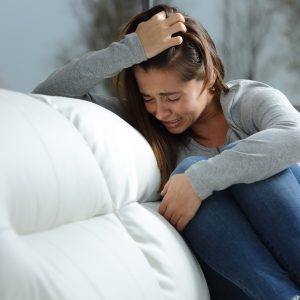 sad girl crying alone on couch in despair hugging knees