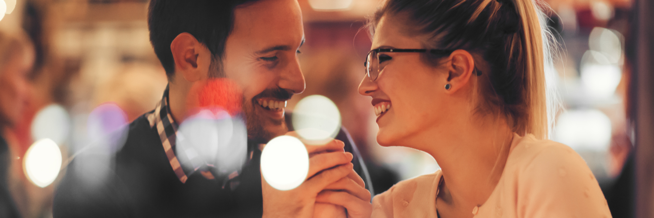 man and woman laughing together in a bar