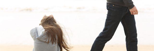 Man walks away from a woman on the beach.