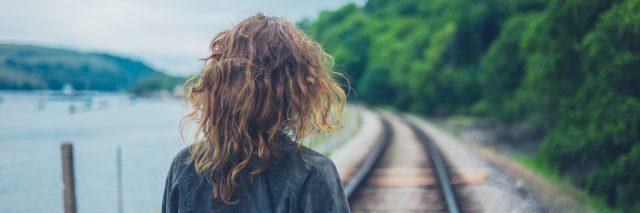 young woman walking along railroad tracks