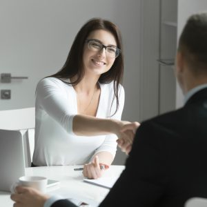 Businessman and businesswoman handshaking over office desk.
