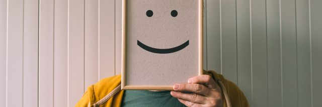 man hiding face with whiteboard with smile drawn on