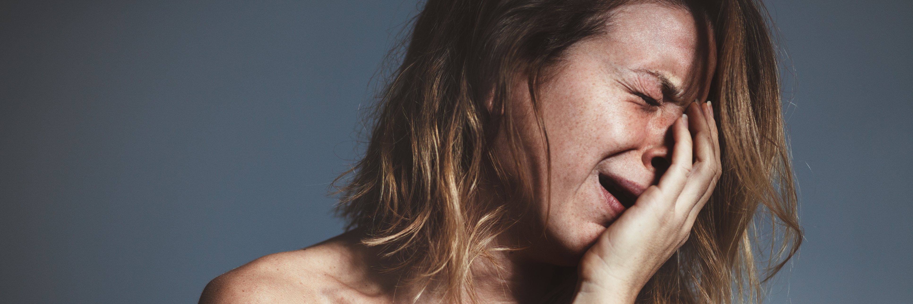 young woman in distress crying on gray background
