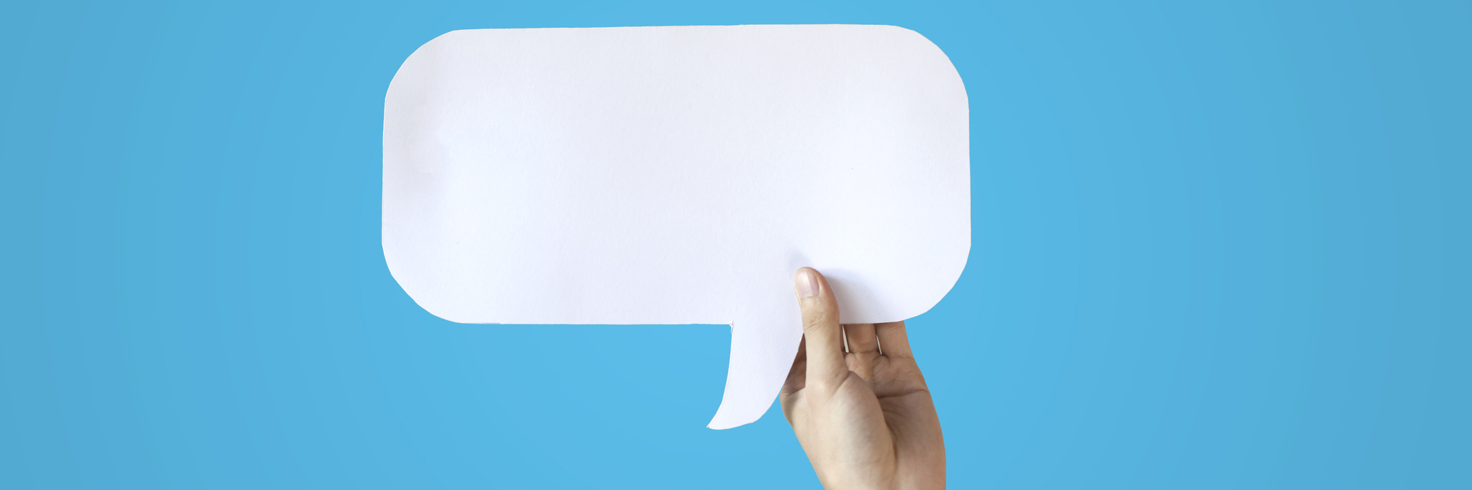 Speech bubble being held in front of blue background.