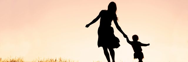 Silhouette of a happy mother and her baby daughter holding hands, and running and dancing outside at sunset.