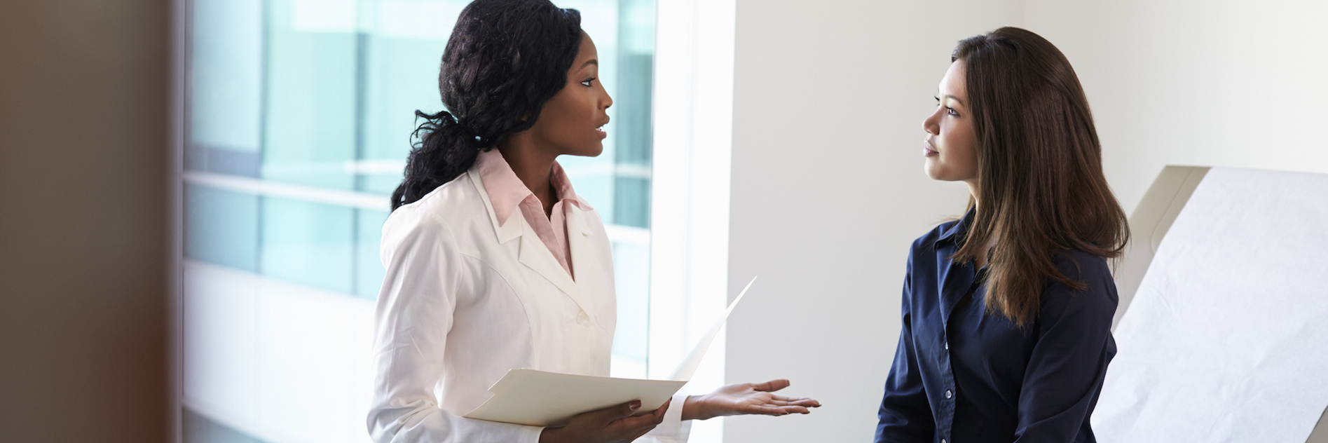 Doctor meeting with patient in exam room