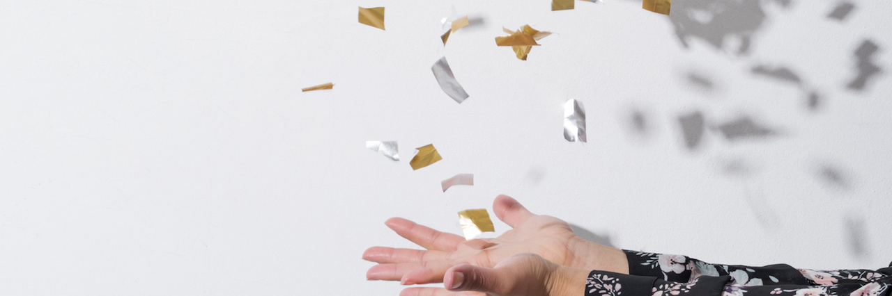 a woman tossing up confetti