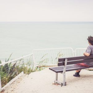 Man sitting on bench overlooking sea.