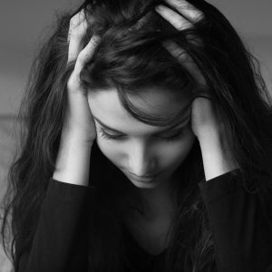 black and white photo of a woman sitting on her bed and holding her head