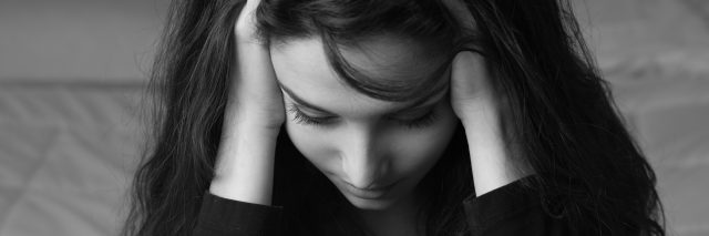 black and white photo of woman holding her head in pain