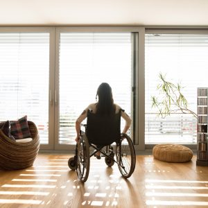 Young disabled woman in wheelchair at the window at home in a living room.