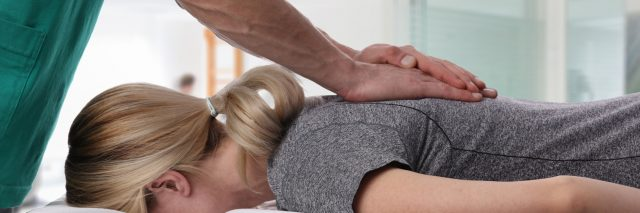 woman having her back adjusted by a chiropractor