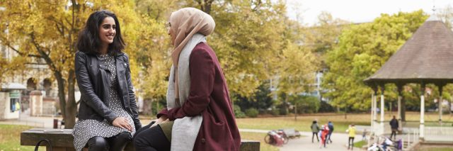 two women talking on a park bench