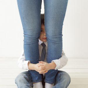 The boy hugs mom's legs, playing hide and seek.