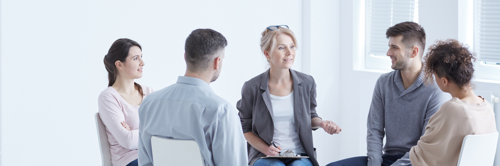 people sitting in circle on chairs in plain room group therapy support