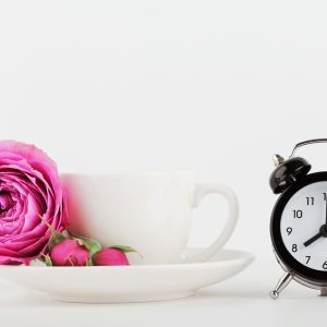 Coffee cup next to a clock.